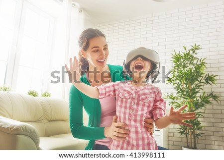 Happy family! Mother and her child daughter play game in virtual reality glasses. - stock photo