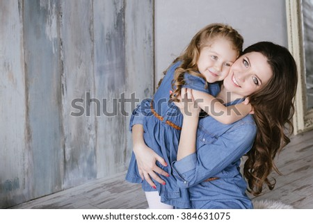 Happy family mother and little daughter hug and playing dressed in denim dress - stock photo
