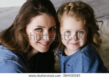 Happy family mother and little daughter hug and smiling dressed in denim dress - stock photo