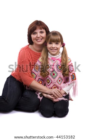 Happy family. Mother and little daughter in winter clothes are smiling. Woman and girl are hugging and posing happily on white background - stock photo