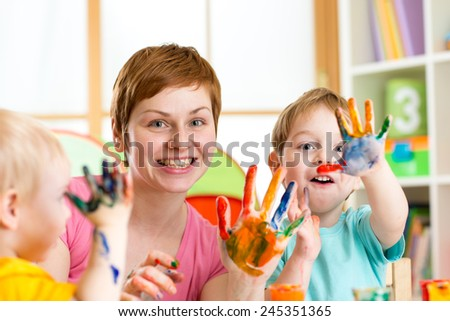 Happy family - mother and sons kids having fun with paints - stock photo