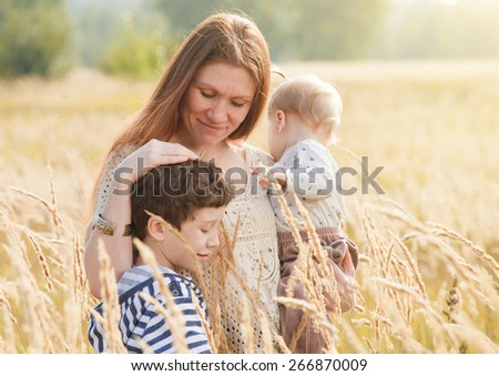 Happy family - Mother and two children, outdoor at the autumn field  - stock photo