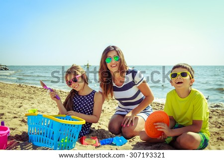 Happy family mother, daughter and son having fun on beach sand. Parent mom and children kids with toys at sea. Summer vacation holidays relax and happiness.