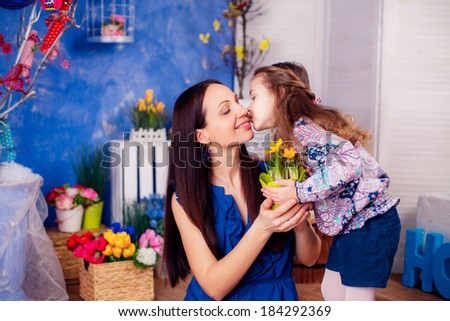 happy family. mother daughter in the room. daughter kissing mother. Mother's Day. March 8, International Women's Day.