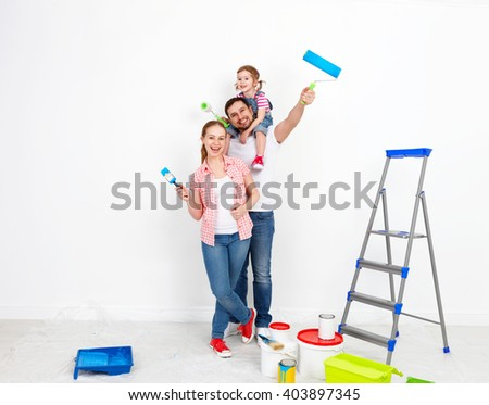 happy family mother father and baby daughter are doing repairs paint wall at home - stock photo