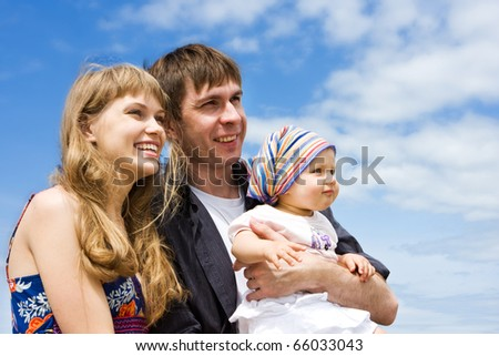 Happy family - mother, father and daughter. Blue skies on the background.