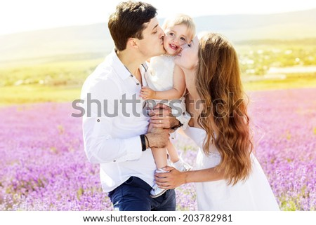 Happy family mother, father and daughter having fun in lavender field - stock photo