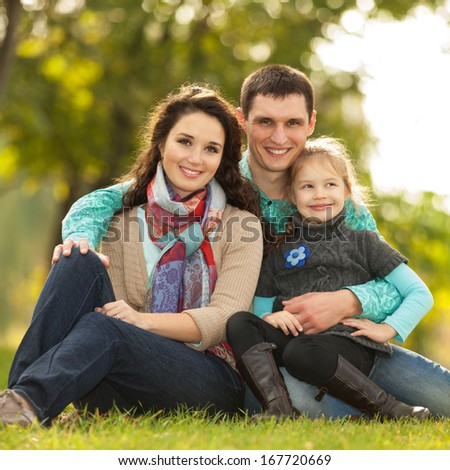 Happy family, mother, father and daughter in the park - stock photo