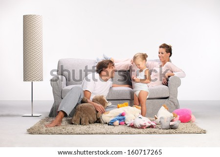 happy family, mother, father and daughter, mom and dad playing with his daughter on the carpet in the living room - stock photo