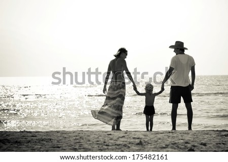 Happy family mother father and little son on sandy beach having fun - stock photo