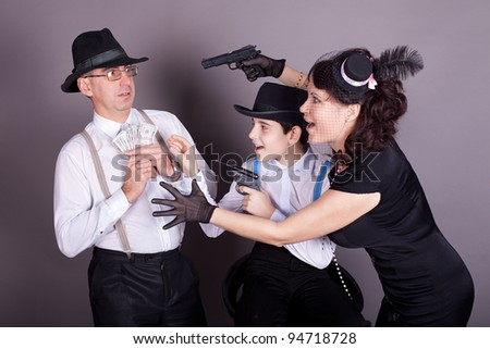 Happy family mother, father and son in the form of gangsters. Studio shot. - stock photo