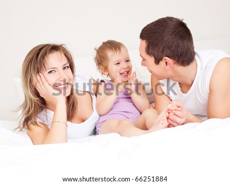 happy family, mother ,father and their baby on the bed at home (focus on the woman) - stock photo