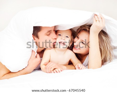 happy family, mother ,father and their baby under the blanket on the bed at home (focus on the man) - stock photo