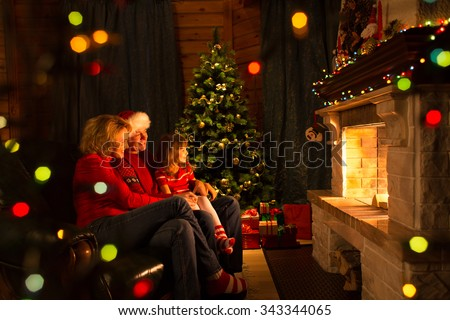 Happy family - mother, father and their daughter by a fireplace on Christmas