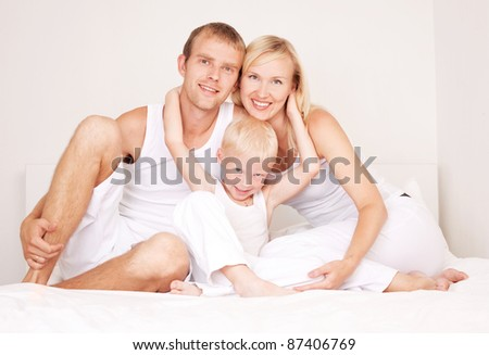 happy family: mother ,father and their son on the bed at home