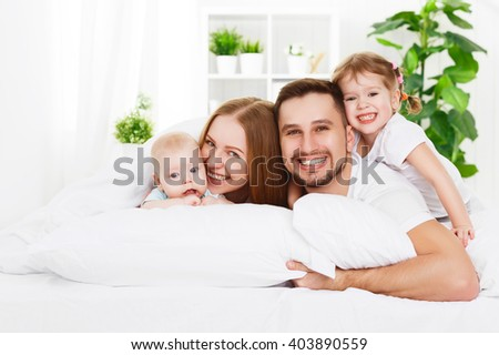 happy family mother, father and two children at home in bed - stock photo