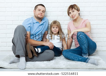 happy family mother, father and two children playing and cuddling at home on the floor