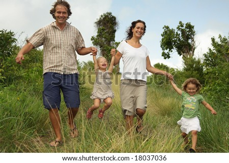 Happy family: mother, father and two daughters having fun on green meadow.