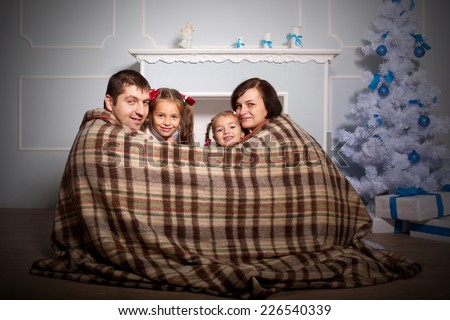 Happy family, mother, father and two kids sitting near the fireplace wrapped in a plaid. - stock photo