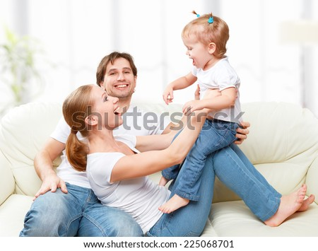 Happy family mother, father, child baby daughter at home on the sofa playing and laughing - stock photo