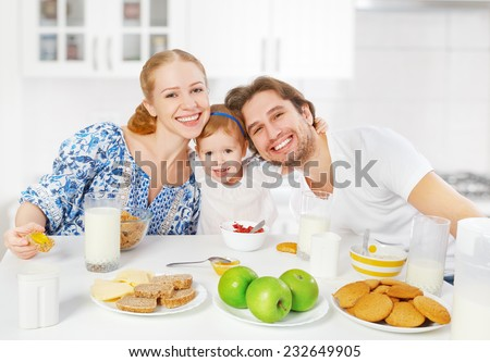 Happy family mother, father, child baby daughter having breakfast at home - stock photo
