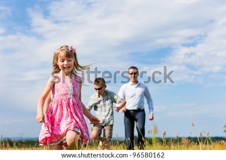 Happy family - mother, father, children - playing on a meadow in summer under blue sky - stock photo