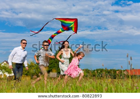 Happy family - mother, father, children - running over a green meadow in summer; they fly a kite - stock photo