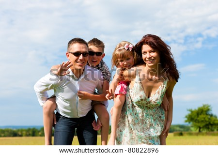 Happy family - mother, father, children - standing on a meadow in summer piggyback the kids - stock photo
