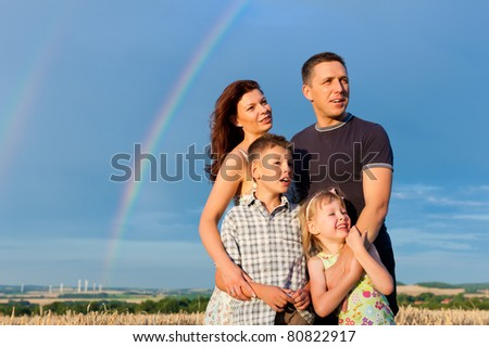 Happy family - mother, father, children - standing under a Rainbow in summer looking into a glorious future - stock photo