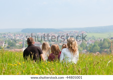 Happy family - mother, father, three children - sitting in a meadow in spring  or early summer, looking over the countryside, a village is to be seen - stock photo