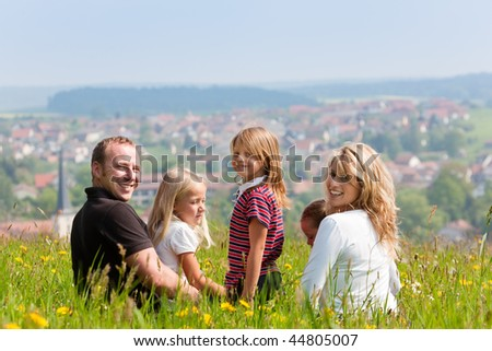 Happy family - mother, father, three children - sitting in a meadow in spring  or early summer, looking at the viewer, in the background is a village - stock photo