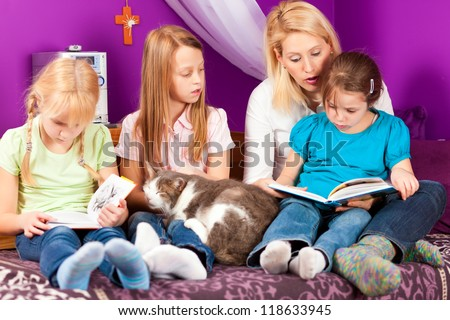 Happy family - mother is reading a book, she and the children are sitting in a kid's room - stock photo