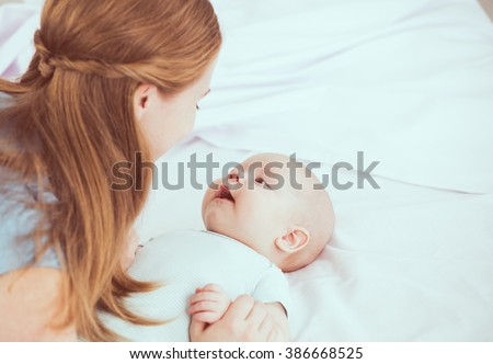 happy family mother playing in bed with newborn baby - stock photo