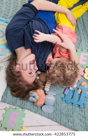 Happy family mother playing with her baby - stock photo