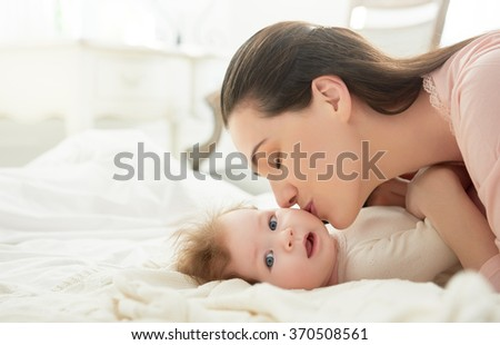 happy family. mother playing with her baby in the bedroom. - stock photo