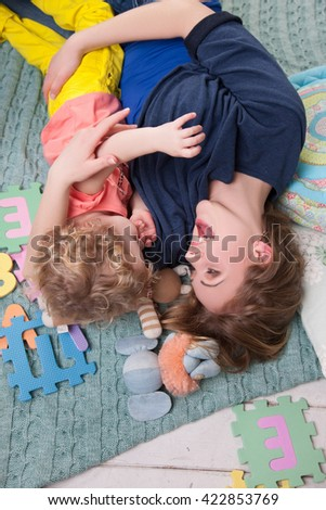 Happy family mother playing with her baby.Joyful Mom and baby playing on the floor - stock photo