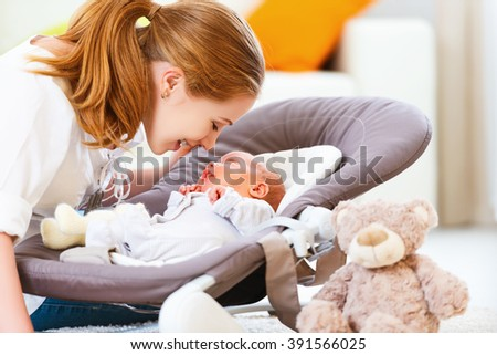 happy family. mother plays and laughs with her newborn baby - stock photo