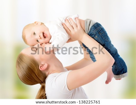 happy family. Mother throws up  baby, playing at home - stock photo