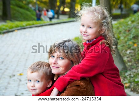 Happy family (mother with children) in golden autumn city park - stock photo