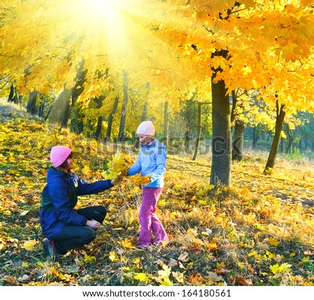 Happy family (mother with daughter) walking in golden maple sunshiny autumn park - stock photo