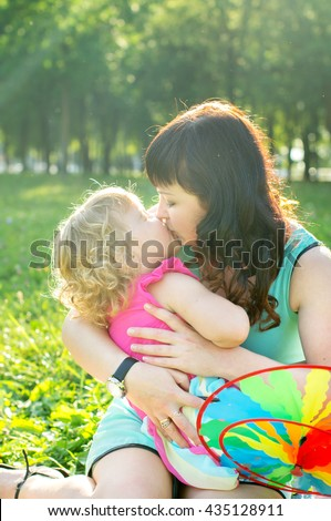 Happy family mother with her daughter on the nature, kiss - stock photo