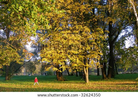Happy family (mother with small girl) in golden autumn city park - stock photo
