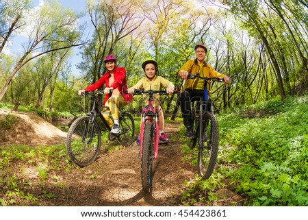 Happy family mountain biking on forest trail - stock photo