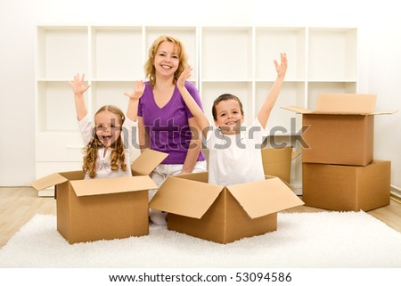 Happy family moving into a new home - with cardboard boxes in an empty room - stock photo