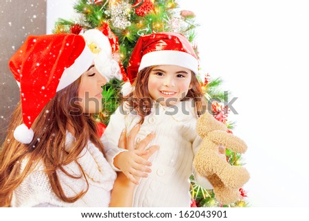 Happy family near beautifully decorated Christmas tree, young mother with cute daughter wearing red Santa hat, copy space, winter holiday - stock photo