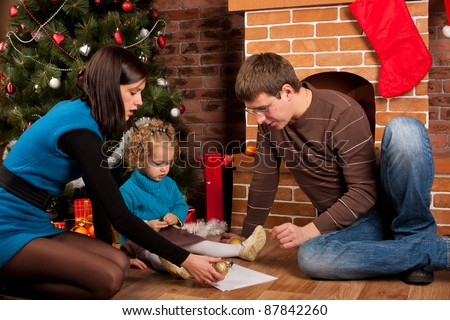 Happy family near Christmas tree - stock photo