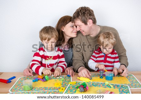 Happy family of a four having fun with modeling clay at home - stock photo