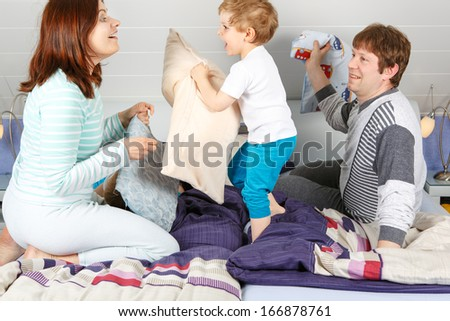 Happy family of a three having fun in pajamas at home in bed and fighting with pillows - stock photo