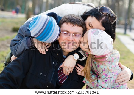 Happy family of 4 celebrating closeup portrait: Parents with two children having fun hugging & kissing father who is happy smile & looking at camera on spring or autumn day outdoors background - stock photo