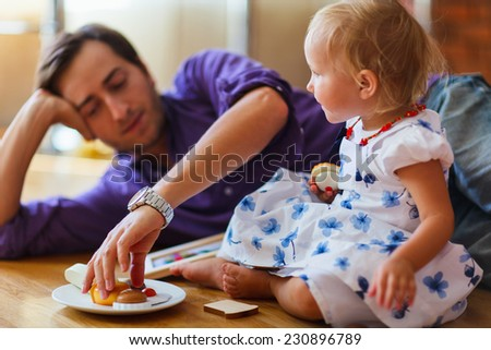 Happy family of  father and his adorable little daughter playing together at home - stock photo